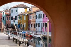 Typical street scene showing brighly painted houses besides canal on the island of Burano, Venice. Burano, Italy. Typical street scene showing brighly painted Royalty Free Stock Photos