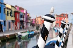 Typical street scene showing brighly painted houses, mooring posts and canal on the island of Burano, Venice. Burano, Italy. Typical street scene showing black Royalty Free Stock Photo