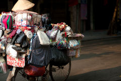 Typical street vendor in Hanoi,Vietnam. HANOI,VIETNAM-OCT 12 : Daily life of the appliance vendors sell on her bicycle in the typical street near old town on Royalty Free Stock Photo