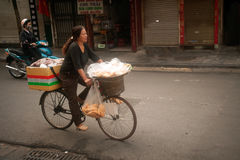 Typical street vendor in Hanoi,Vietnam. HANOI,VIETNAM-OCT 12 : Daily life of the appliance vendors sell on her bicycle in the typical street near old town on Stock Image