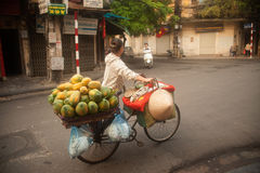 Typical street vendor in Hanoi,Vietnam. HANOI,VIETNAM-OCTOBER 12 : Daily life of the fruit vendors sell on her bicycle in the typical street near old town on Royalty Free Stock Image