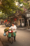 Typical street vendor in Hanoi,Vietnam. HANOI,VIETNAM-OCTOBER 12 : Daily life of the fruit vendors sell on her bicycle in the typical street near old town on Royalty Free Stock Photos
