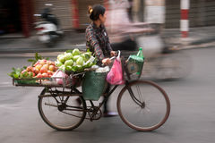 Typical street vendor in Hanoi,Vietnam. HANOI,VIETNAM-OCTOBER 12 : Daily life of the fruit vendors sell on her bicycle in the typical street near old town on Royalty Free Stock Photo
