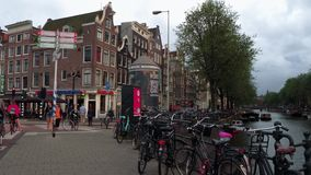 Typical street view in the city of Amsterdam at Central Station - AMSTERDAM - THE NETHERLANDS - JULY 19, 2017. Typical street view in the city of Amsterdam at stock footage