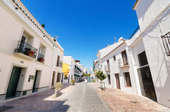 Typical street with white houses in the touristic village of Nerja. Royalty Free Stock Photo