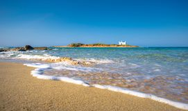 Typical summer image of an amazing pictorial view of a sandy beach and an old white church in a small isl. And at the background, Malia, Crete, Greece stock image