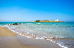 Typical summer image of an amazing pictorial view of a sandy beach and an old white church in a small isl Royalty Free Stock Photos