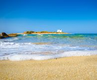 Typical summer image of an amazing pictorial view of a sandy beach and an old white church in a small isl Royalty Free Stock Photo