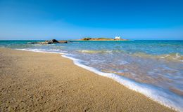 Typical summer image of an amazing pictorial view of a sandy beach and an old white church in a small isl. And at the background, Malia, Crete, Greece Stock Photography