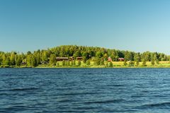 Typical Swedish countryside farm by a lake in beautiful summer s. Typical Swedish countryside farm located by a lake with green fields and surrounding forest. On royalty free stock images