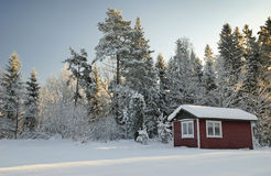 Typical Swedish winter landscape. Swedish red arbor in front of frozen forest Royalty Free Stock Photography
