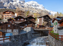 Typical Swiss houses along the Dala river on a spring day in Leukerbad, Valais canton, Switzerland.  stock photography