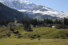 Typical Swiss village with snow on the mountains Royalty Free Stock Photography
