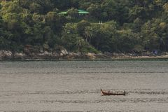 Typical Thai boat in front of an island in the bay of Phang Nga phuket thailand Stock Photography