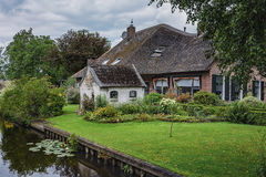 Typical thatched cottage with beautiful garden along a canal in Giethoorn, known as Dutch Venice Stock Image