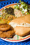 Typical tinidad food platter. Platter of typical local trinidad food bodi fry bake saltfish cod with fried accra bread fritters and vegetables with jonnycake Stock Photo