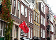 Typical Touristy Amsterdam. I amsterdam flag waves from a historical townhouse which sits on the edge of a canal Royalty Free Stock Images