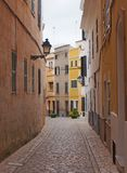Typical town street in ciutadella menorca with winding curved cobbled road old traditional painted houses and street lamps stock photography