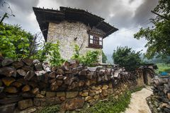 Traditional Bhutanese farmhouse , with firewood on the fence wall , Ura Valley , Bhutan. A typical traditional Bhutanese village farmhouse , with firewood on the royalty free stock image