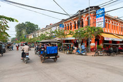 Typical traffic passes a colorful building in Siem Reap, Cambodi Stock Image