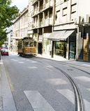 Typical tram going up a street in the center of Porto with a bend in the rails. Porto, Portugal. August 12, 2017: Typical tram going up a street in the center of stock photo