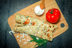 Typical Turkish meal Gozleme with herb and cheese on light wooden cutting board on black table. Toned.  stock photos