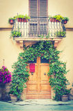 Typical Tuscan door with plants, and a balcony Stock Photos