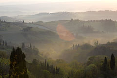 Typical Tuscan landscape. Fog and typical Tuscan landscape - a view of a villa on a hill, a cypress alley and a valley with vineyards, province of Siena. Tuscany Stock Photo