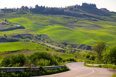 Typical Tuscan landscape. Road and view of a villa on a hill with green fields at sunny day. province of Siena. Tuscany, Italy Stock Images