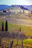 Typical Tuscan landscape. A view of a villa on a hill, a cypress alley and a valley with vineyards, province of Siena. Tuscany, Italy Royalty Free Stock Images