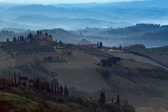 Typical Tuscan landscape. A view of a villa on a hill, a cypress alley and a valley with vineyards, province of Siena. Tuscany, Italy Stock Images