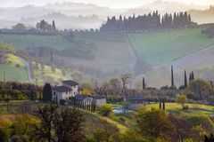 Typical Tuscan landscape. A view of a villa on a hill, a cypress alley and a valley with vineyards, province of Siena. Tuscany, Italy Royalty Free Stock Photo