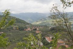 Typical Tuscany landscape with hills, green trees and houses, Italy. The view of typical Tuscany landscape with hills, green trees and houses royalty free stock images