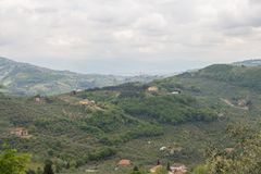 Typical Tuscany landscape with hills, green trees and houses, Italy. The view of typical Tuscany landscape with hills, green trees and houses stock photography
