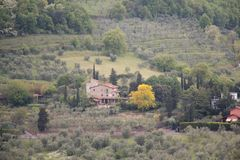 Typical Tuscany landscape with hills, green trees and mansion, Italy. The view of typical Tuscany landscape with hills, green trees and mansion stock photo