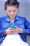Typical Tween Communication. A closeup of a typical young little brunette tween girl wearing a denim jean jacket texting on the phone. Shallow depth of field Stock Photo