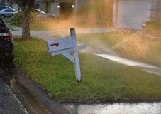 Typical US mail box is getting wet due to sprinklers stock images