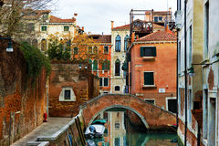 Typical Venetian canal with bridge and moored boats Royalty Free Stock Photos