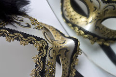 A typical Venetian carnival mask, gold with black, is reflected in the mirror Stock Photography