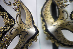 A typical Venetian carnival mask, gold with black, is reflected in the mirror Stock Photos