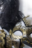 A typical Venetian carnival mask, gold with black, is reflected in the mirror. Looking into a mirror. Stock Photography