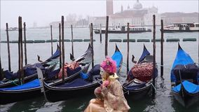 A Typical Venetian Mask with gondolas, Venice Lagoon, Italy. A Typical Venetian Mask with gondolas and Venice Lagoon on the background, Venice, Italy stock video footage