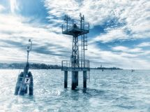Typical venice buoy and navigation light in the lagoon. Typical venice buoy and navigation light in the laggon with sbright sunny summer sea and clouds with Royalty Free Stock Photo