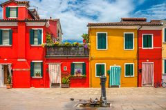 Typical vibrant Burano house with striped curtains on front door. Burano house with striped curtains on front door in summer Stock Images