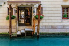 Weathered building facade on a picturesque canal in Venice Italy. Typical view of a building facade in Venetian Gothic architecture style with a dock on a royalty free stock photo