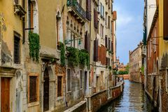 Weathered building facade on a picturesque canal in Venice Italy. Typical view of a weathered building facade on a picturesque canal in Venice, Italy stock photo