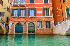 Weathered building facade on a picturesque canal in Venice Italy. Typical view of a weathered building facade on a picturesque canal in Venice, Italy royalty free stock photos