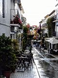 A typical village alley in Spain with cafes, flowers and people walking after rain. White cloudy skies Royalty Free Stock Photography