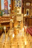 Burning candle in the church in front of the icons Stock Photo