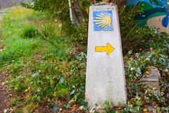 Typical Way of Saint James Camino de Santiago milestone with a yellow shell and yellow arrow Stock Image